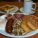 É o famoso Full English breakfast, onde não falta feijão, salsichas, bacon, ovos, cogumelos, hash browns (uns bolinhos de batata fritos), torradas, além do tradicional chá inglês, oras (Foto: Divulgação)